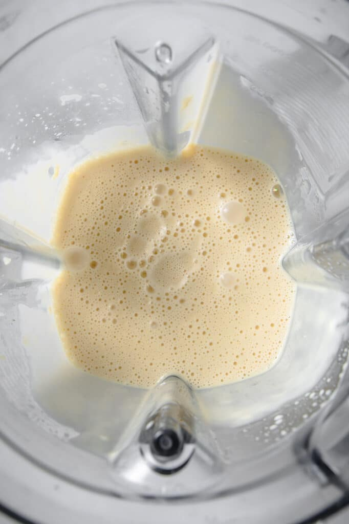 heavy cream, butter and monk fruit sweetener mixture in a blender, atop a marble kitchen counter