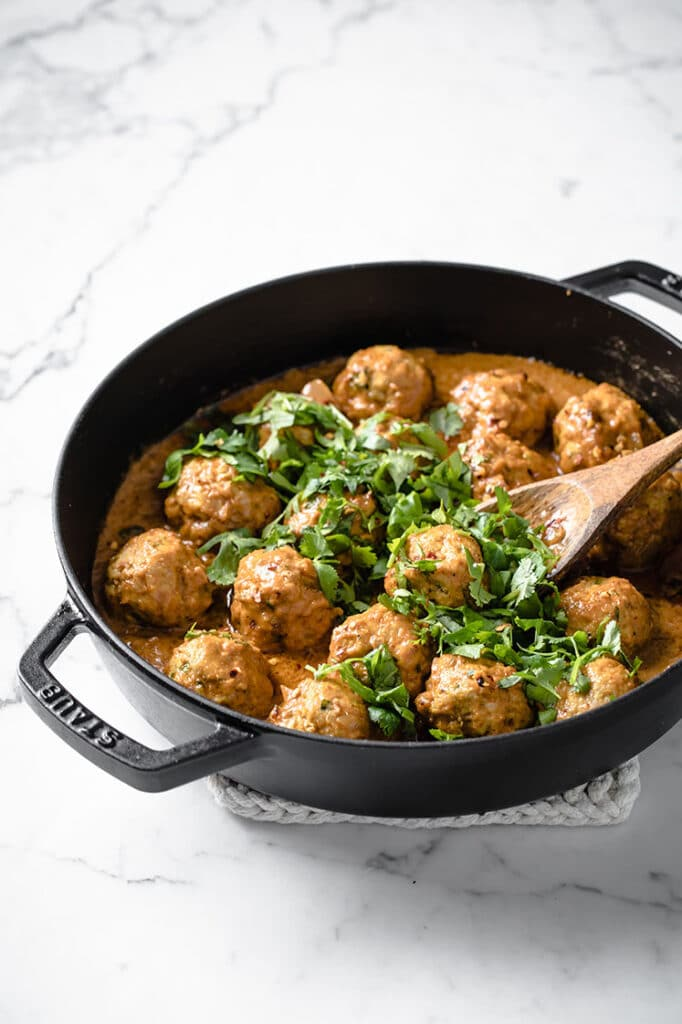 keto thai coconut curry meatballs on a pan garnished with chopped cilantro and basil atop a marble kitchen counter
