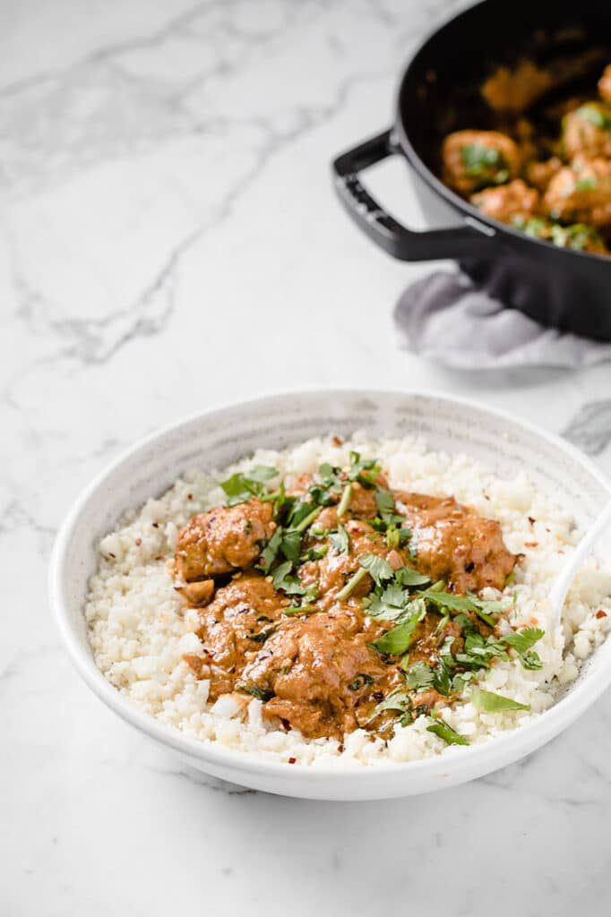 a bowl of cauliflower rice topped with keto thai coconut curry meatballs atop a marble table