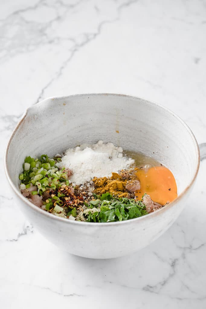 meatballs ingredients in a bowl atop a marble kitchen counter
