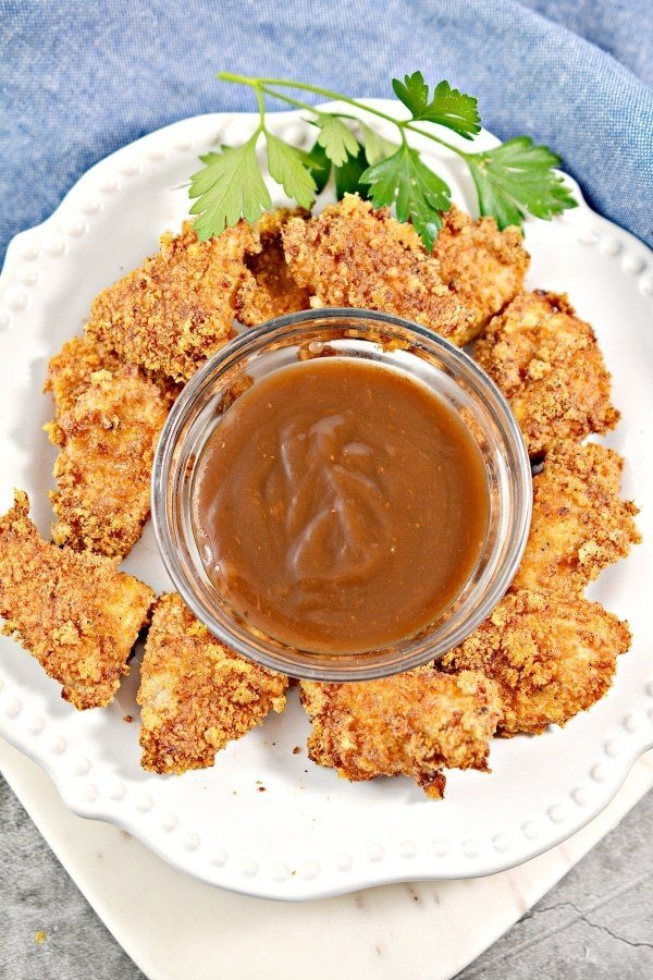 keto chicken nuggets on a plate with a dip in the center atop a kitchen counter