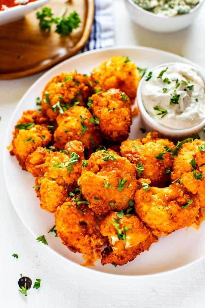 keto cauliflower wings on a plate atop a marble kitchen table
