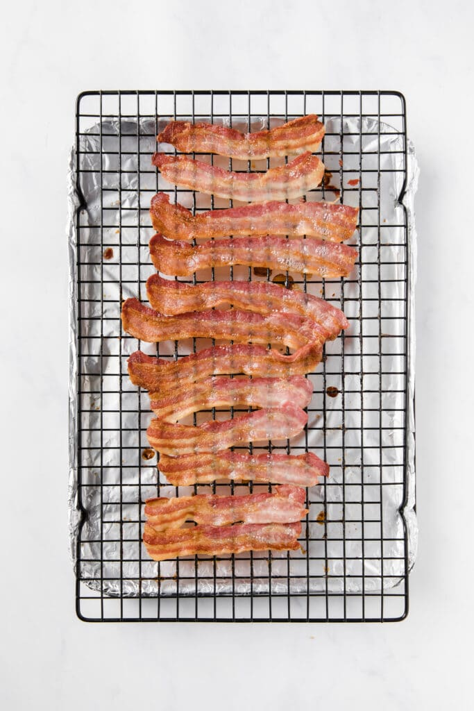 cooked bacon laid on top of a baking rack with a foil underneath