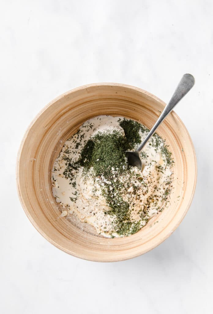 sour cream, mayonnaise, herbs and spices in a mixing bowl