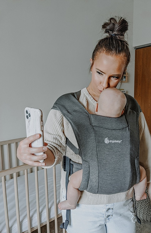 mother carrying baby using ergobaby carrier while taking a photo with cellphone