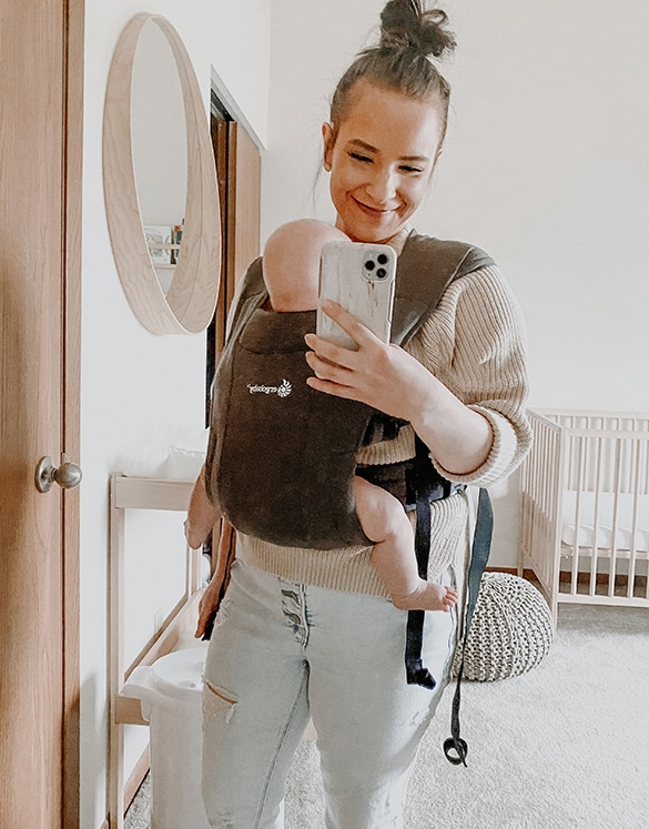 sara nelson taking mirror selfie with cell phone with baby in carrier in nursery