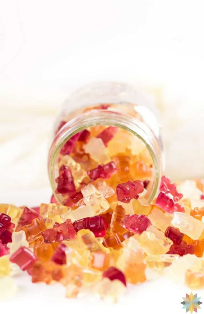a jar full of spilled homemade gummy bears atop a marble kitchen table