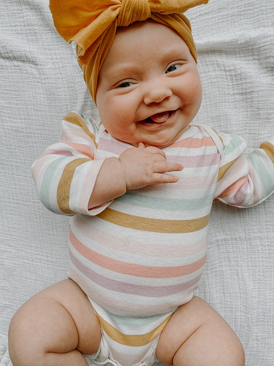 Lucy Nelson smiling and dressed in colored stripe bodysuit and yellow bow