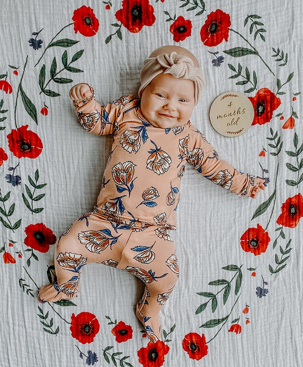 Lucy Nelson in a flower outfit wearing a headband on a flower photo mat with a 4 month old label