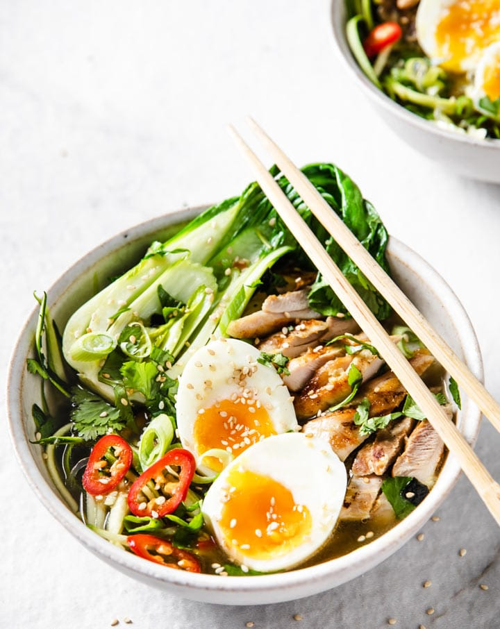 a bowl of low carb keto chicken ramen atop a marble kitchen table