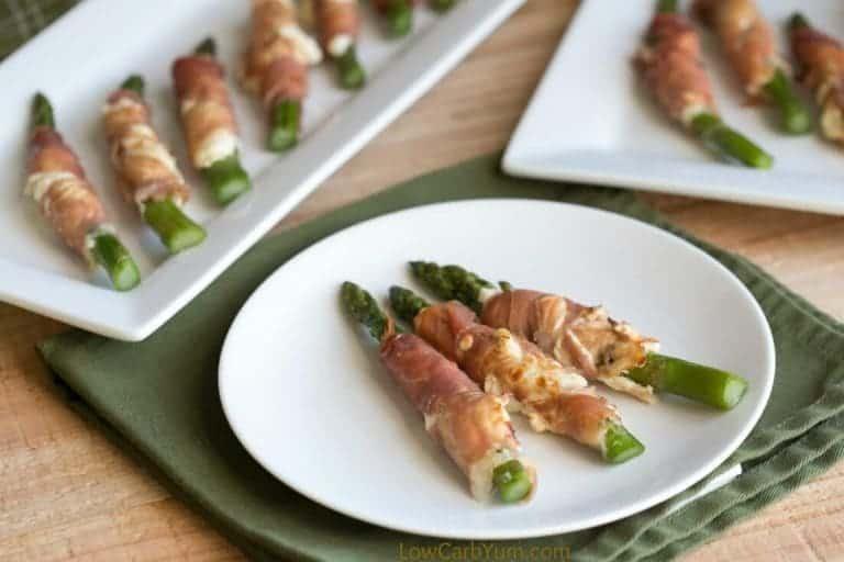prosciutto wrapped bacon asparagus cream cheese on a plate atop a wooden counter