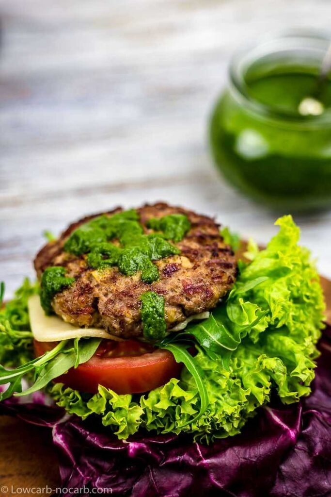 close-up image of bunless bacon grilled burger sitting atop of sliced tomatoes and lettuce