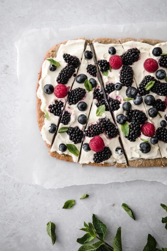 keto fruit pizza on a parchment paper sliced in a triangular shape sprinkled with mint leaves atop a marble table