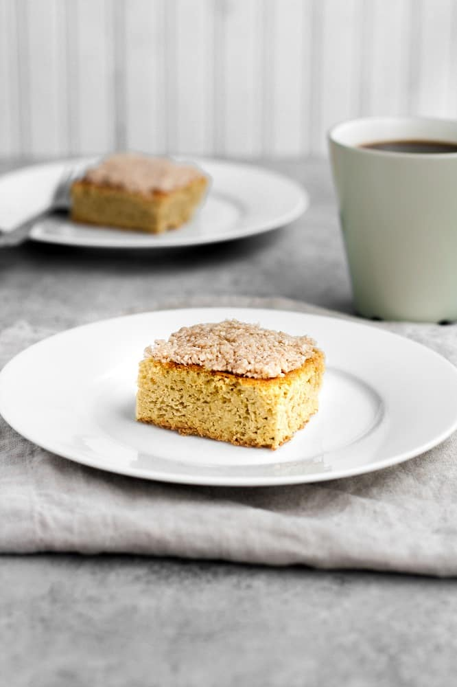 keto coffee cake on a small plate beside a mug of coffee