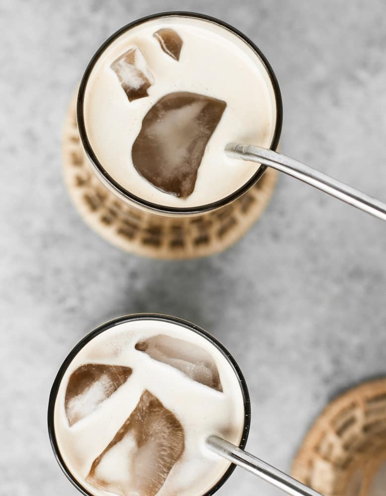 overhead-shot-of-two-glasses-of-Nut-Free-Dairy-Free-Creamy-Cold-Brew-Keto-Coffee-with-ice-and-coasters-and-stainless-steel-straws
