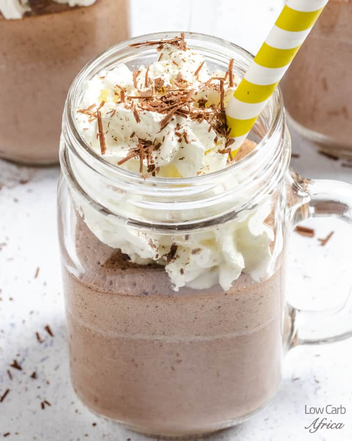 keto summer recipes - a jar of keto chocolate almond protein shake with a yellow striped straw atop a marble table