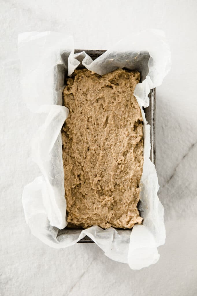 nut-free keto dough in a loaf tin lined with parchment paper atop a marble kitchen counter