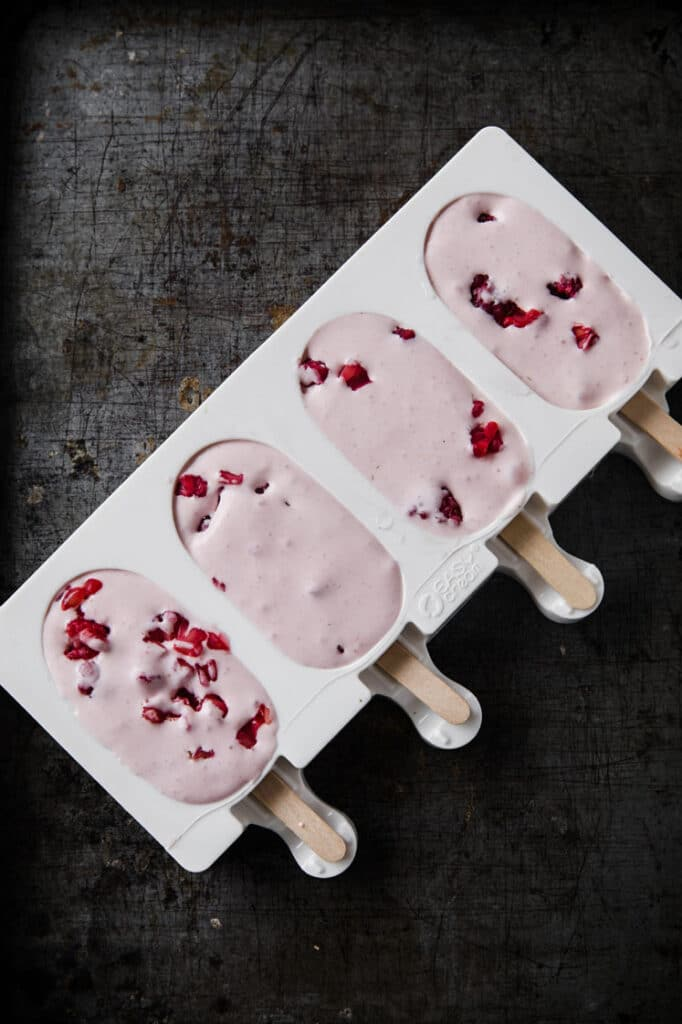 berries and cream popsicle mixture poured in popsicle mold cavities atop a black kitchen counter