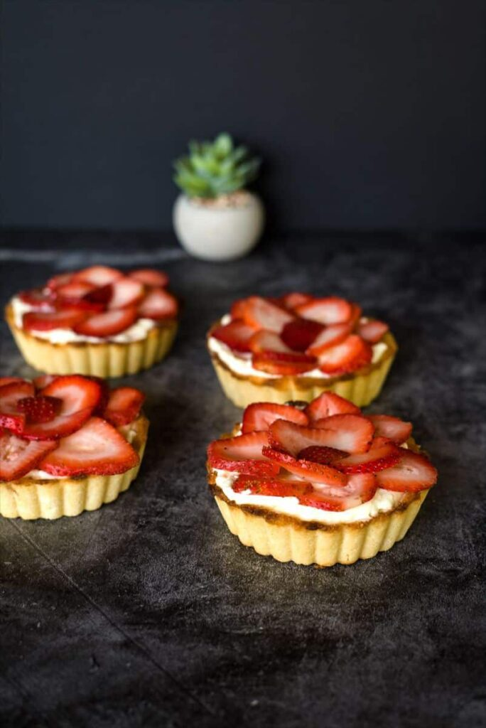 angled shot of 4 low-carb strawberry tarts atop a dark marble table