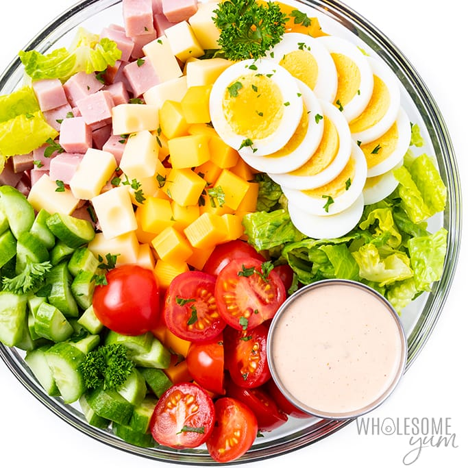 overhead shot of chef salad bowl with cherry tomatoes,eggs, etc. atop a marble kitchen table