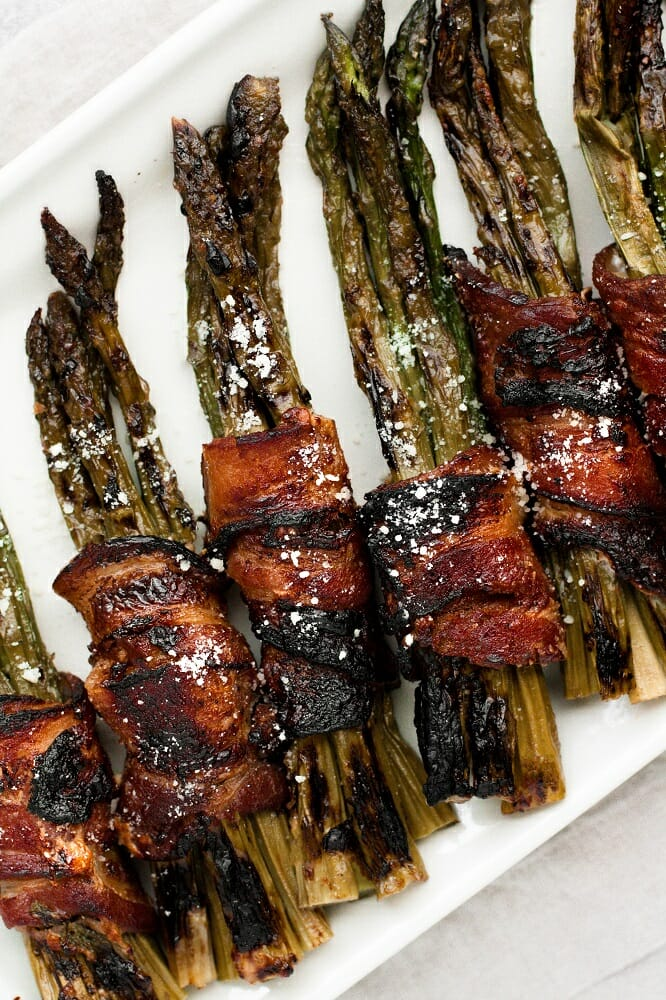 bacon wrapped maple parmesan asparagus bundles in a rectangular plate
