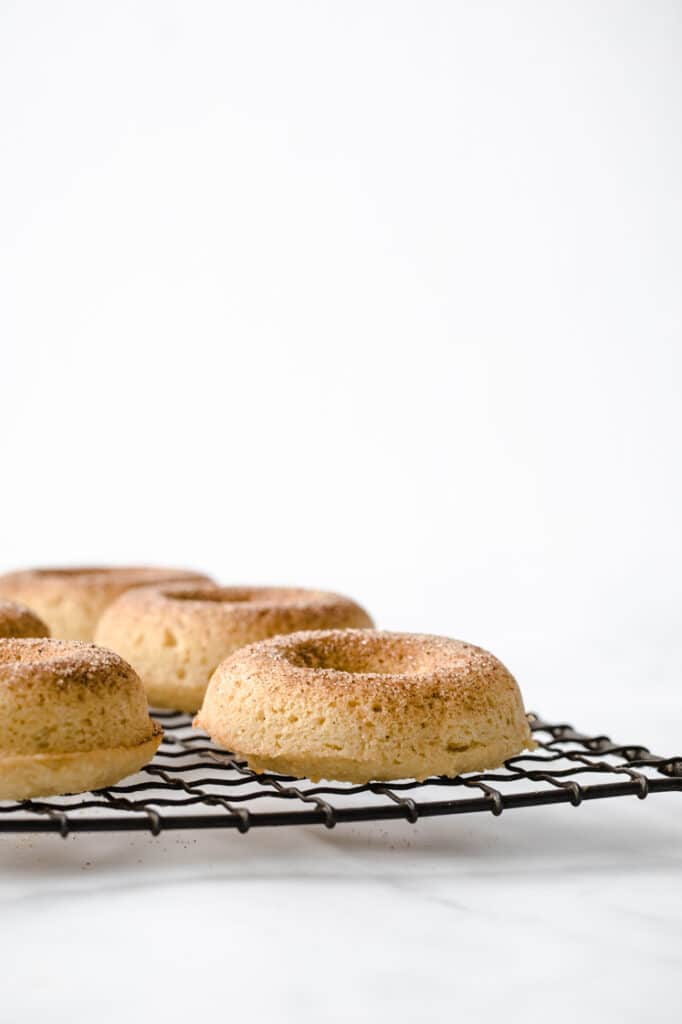 close-up image of freshly baked keto donuts resting on a wire rack atop a marble kitchen counter