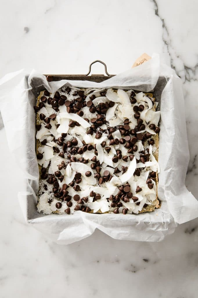 magic bar base topped with shredded coconut and dark chocolate chips in a baking pan atop a marble kitchen counter