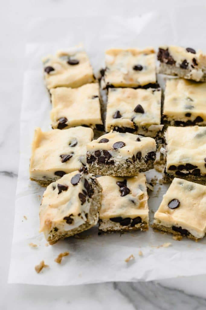 angled overhead image of keto magic bars cut on a baking sheet atop a marble kitchen counter