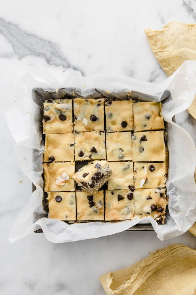 overhead image of keto magic bars cut to small bite sized treats in a baking pan atop a marble kitchen counter