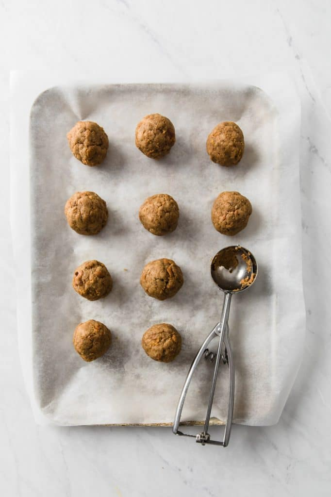 pumpkin pie cake rolled into small balls on a parchment paper-lined baking sheet