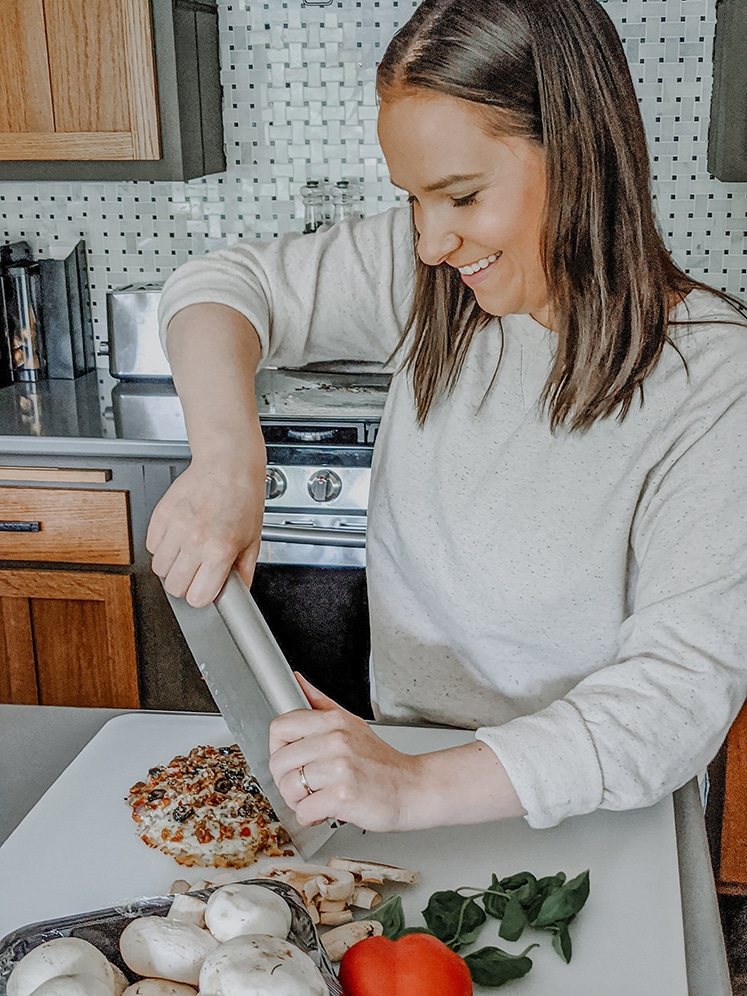 sara nelson cutting cooked pizza with pizza cutter on a cutting board in a kitchen