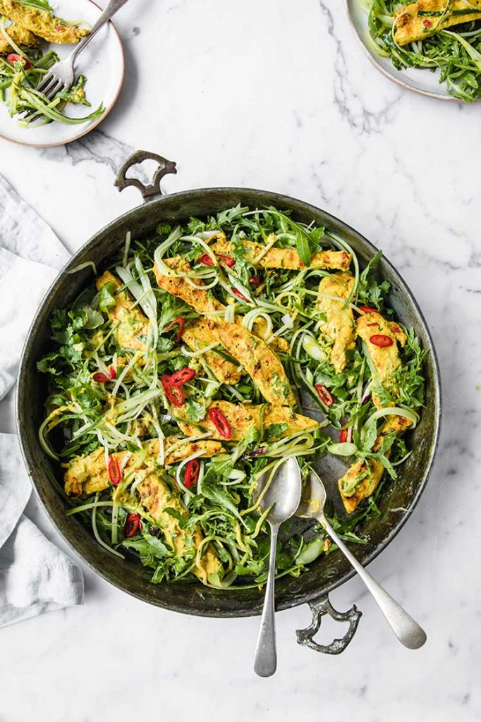 overhead hero image of thai coconut chicken salad on a pan atop a marble kitchen counter with small servings on a plate n the upper left and right corners.