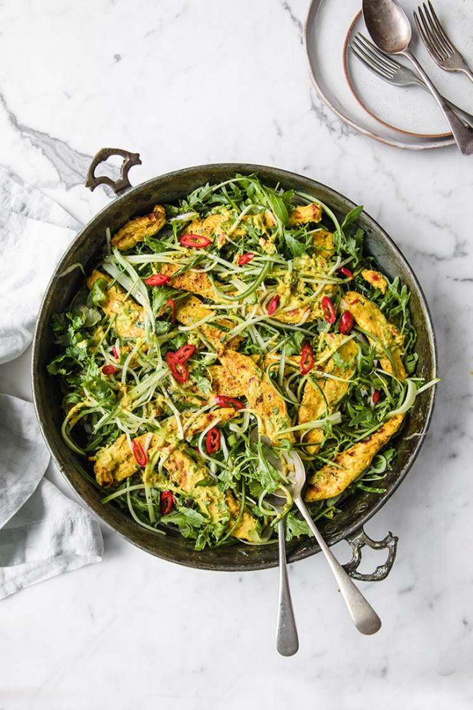 overhead image of a pan filled with thai coconut chicken salad atop a marble kitchen counter