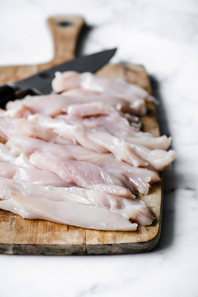 chicken breast cut into strips on a chopping board