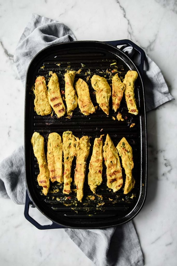 chicken strips cooked on an even layered pan atop a marble kitchen table.