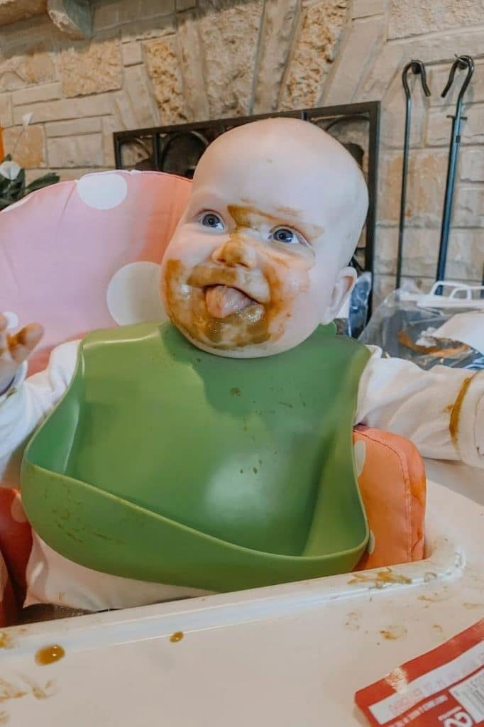 baby lucy on a high chair eating with baby food on her face