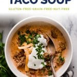 keto slow cooker taco soup in a bowl with a dollop of sour cream and more cheese