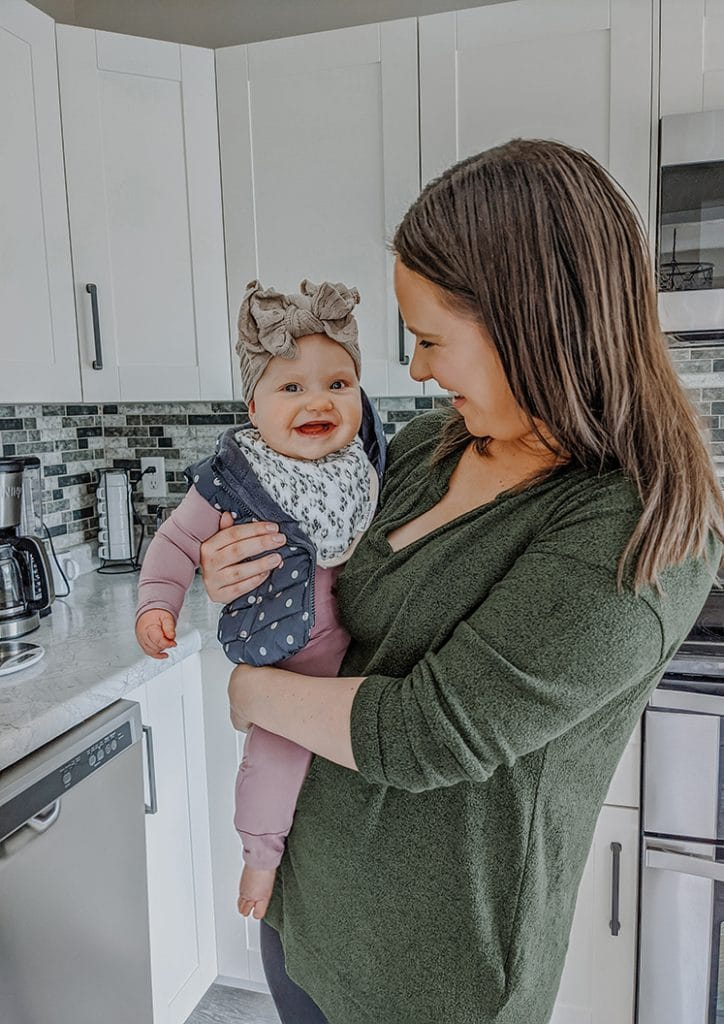 sara nelson holding lucy on her hip in a kitchen with white cabinets and checkered backsplash