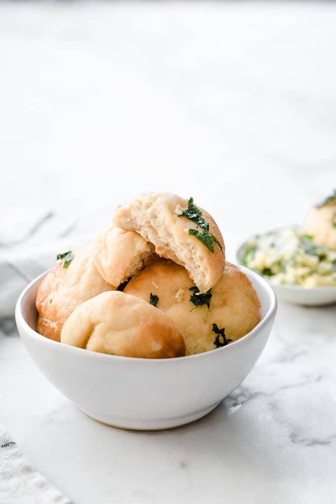 half-eaten keto garlic dough ball on top of a bowl of keto garlic dough balls atop a marble kitchen counter