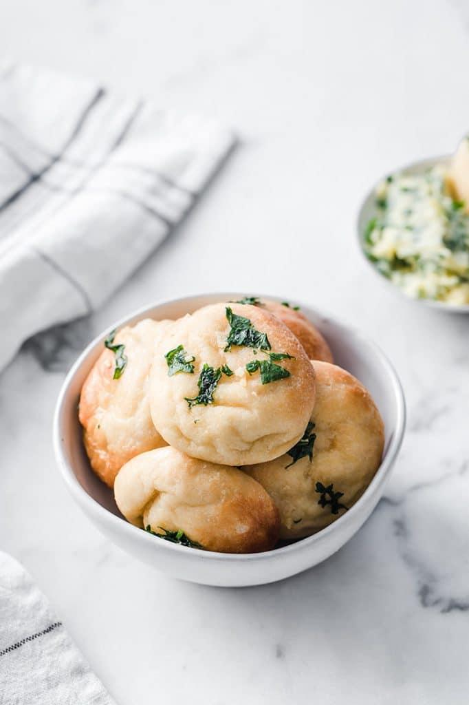 a bowl full of keto garlic dough balls atop marble kitchen counter