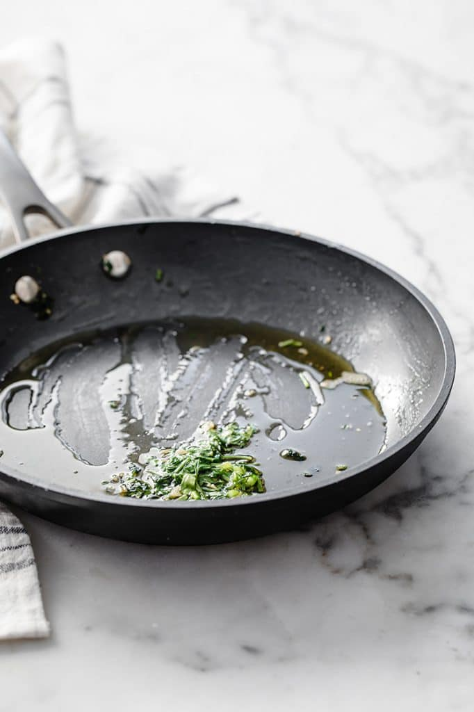 melted garlic butter in a pan atop a marble kitchen table