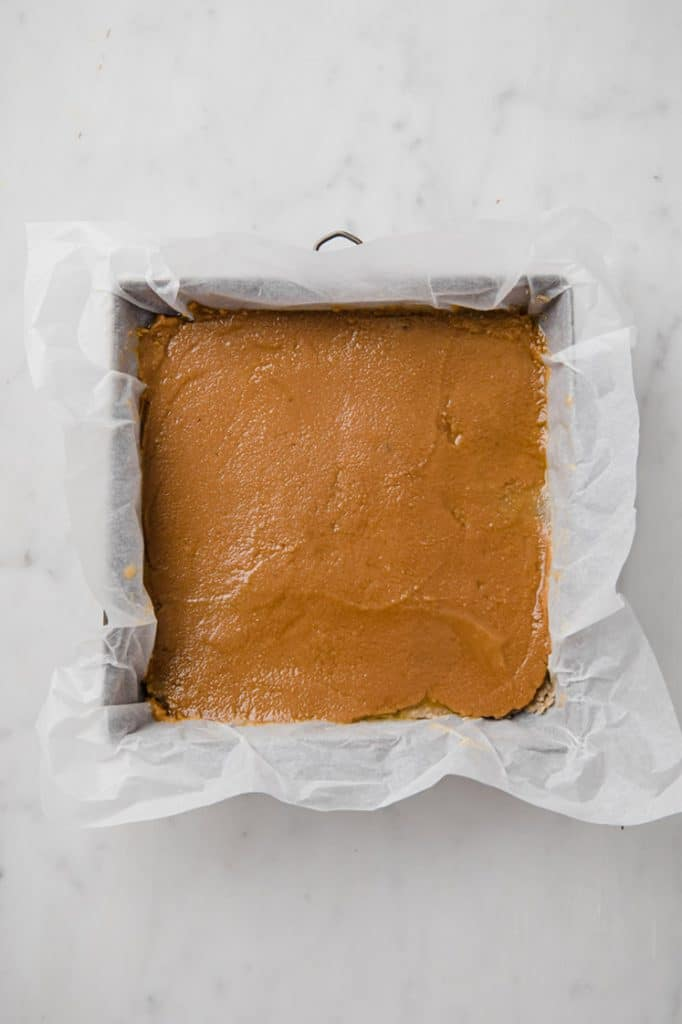 caramel poured on top of base layer in a baking pan with parchment paper coming out of pan