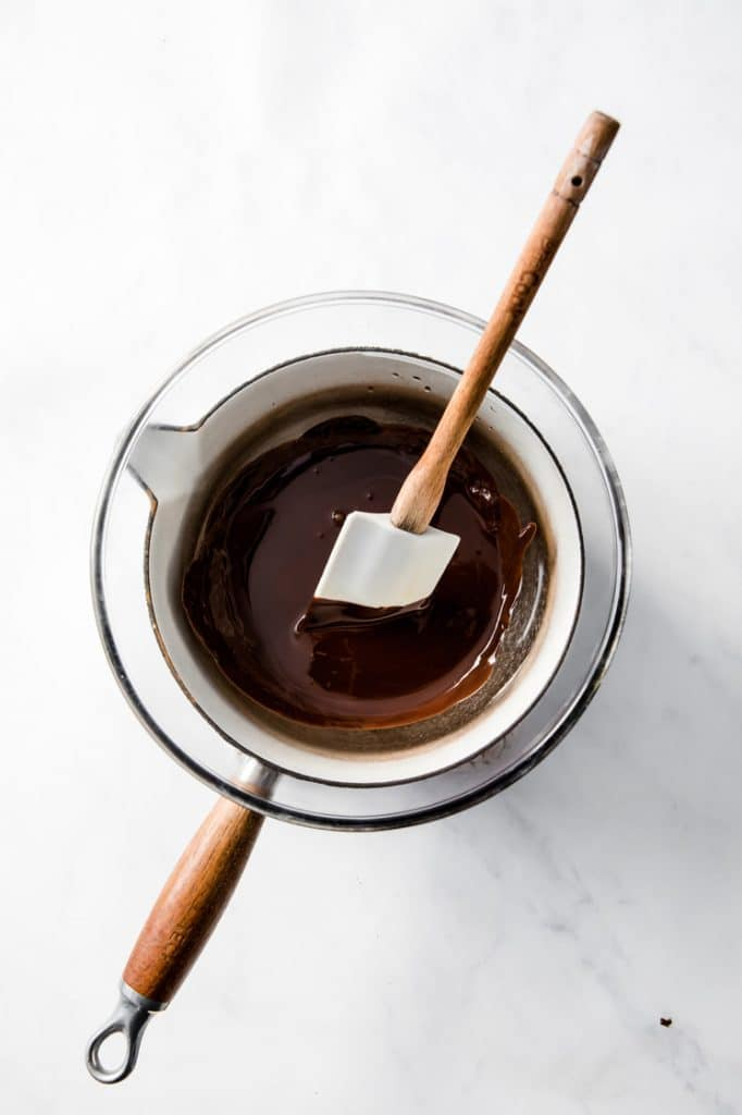 melted chocolate in a pot being stirred with a rubber spatula atop a marble kitchen counter