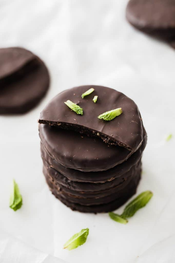 a stack of keto thin mints with the top half eaten with mint leaves sprinkled atop a marble kitchen counter