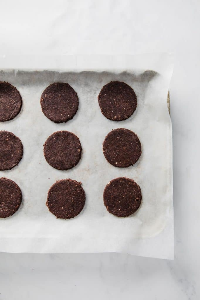 12 thin mint cookie dough on a baking sheet lined with parchment paper atop a marble kitchen counter