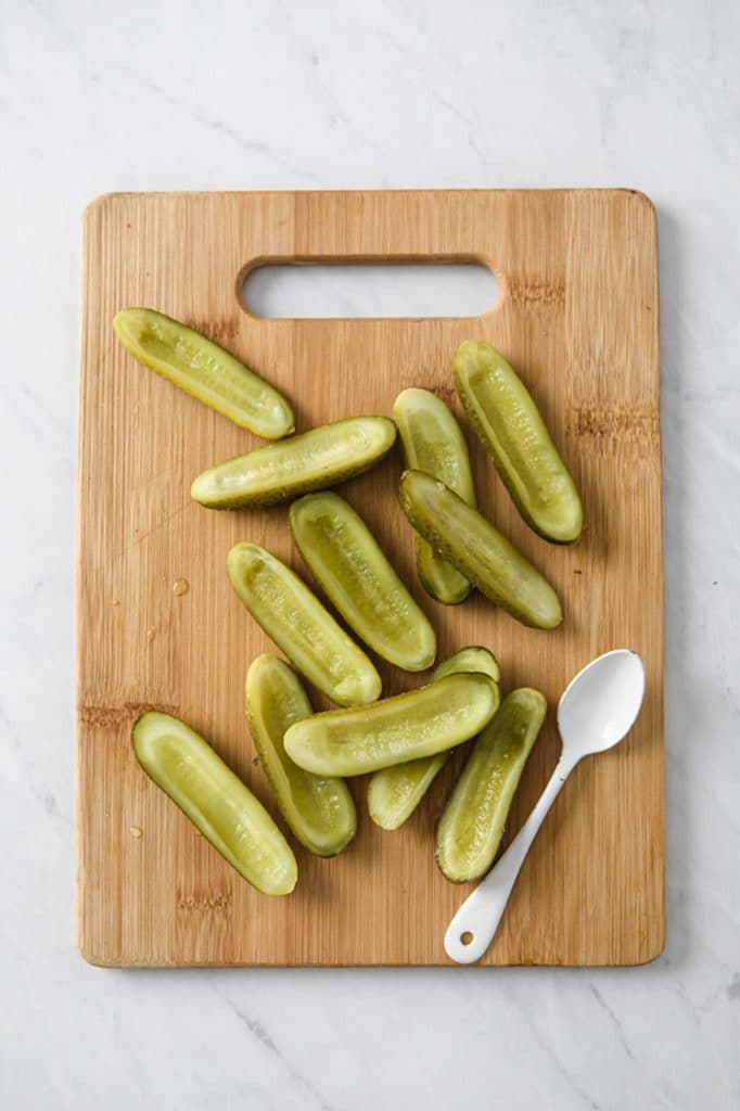 dill pickles sliced in half lengthwise on a wooden cutting board atop a marble kitchen counter