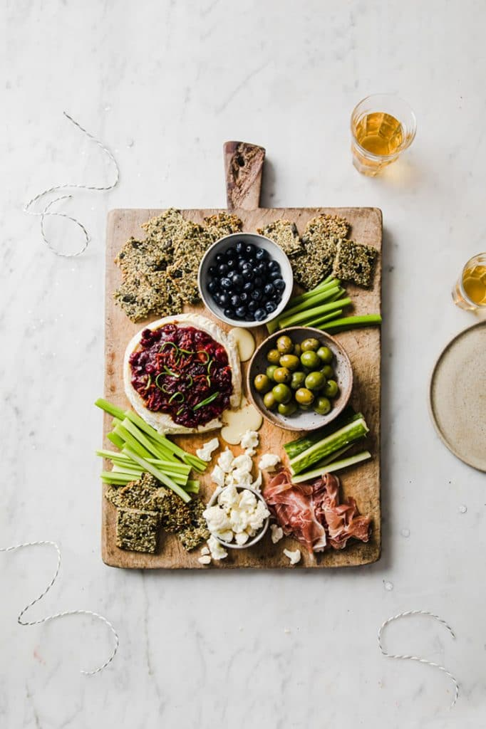 keto baked brie served on a serving board with nut-free crackers, celery, and a bowl of blue berries and olives atop a marble kitchen counter
