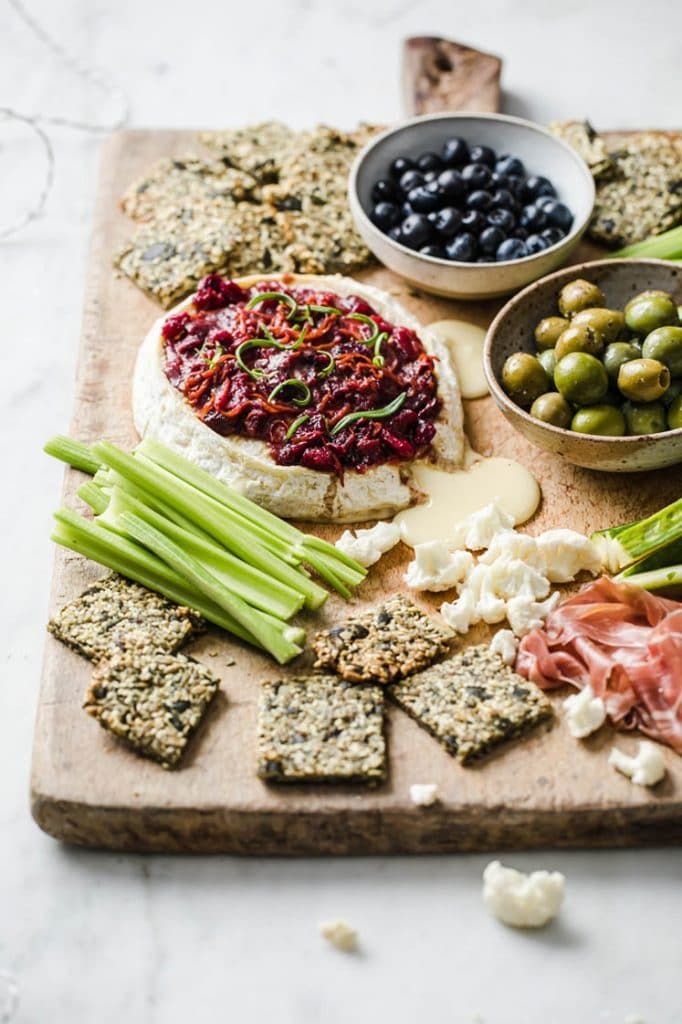angled shot of baked brie with nut-free crackers, celery, a bowl of olives, and a bowl of blue berries on a serving board atop a marble kitchen counter