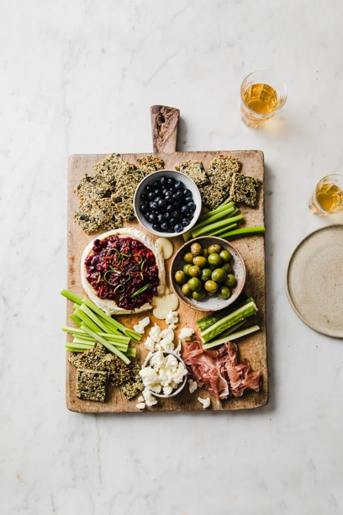 overhead shot of baked brie with nut-free crackers, celery, a bowl of olives, and a bowl of blue berries on a serving board atop a marble kitchen counter