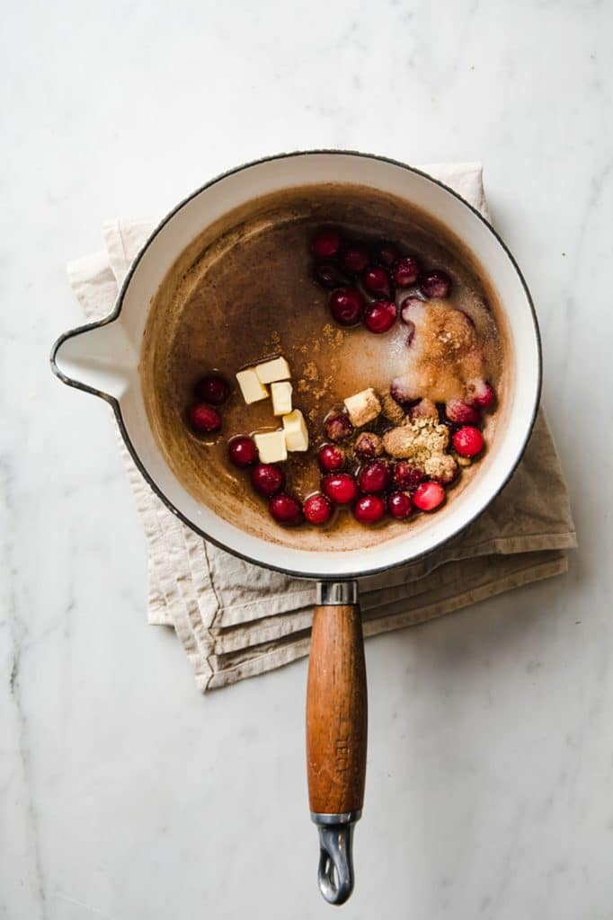overhead image of butter, cranberries, , monk fruit sweetener, cinnamon, cardamom pods, nutmeg, ginger, and water in a sauce pan atop a marble kitchen counter